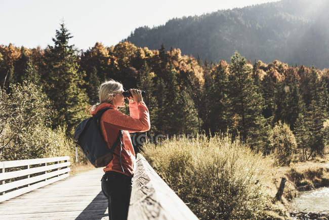Austria, Alps, woman on a hiking trip looking through binoculars — Foto stock