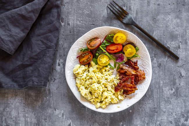 Яєчня з смаженим беконом і салатом з томатами, низьким вмістом вуглеводів, зверху — стокове фото