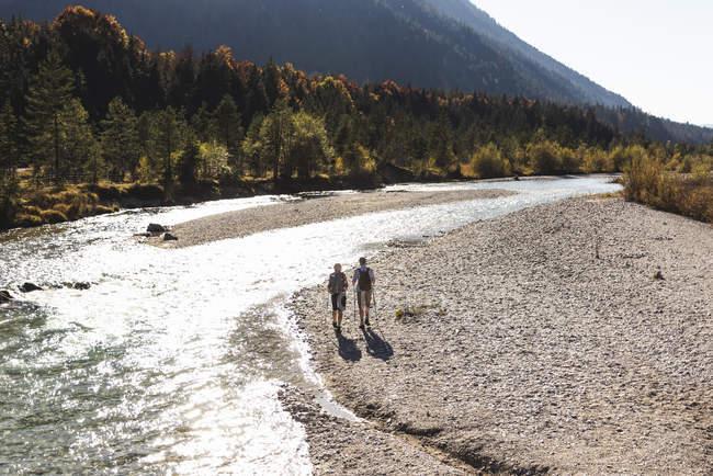 Austria, Alps, couple on a hiking trip walking along a brook — Stock Photo