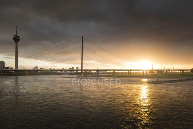 Alemania, Duesseldorf, Oberkassel Puente con Media Harbour en el fondo al atardecer - foto de stock