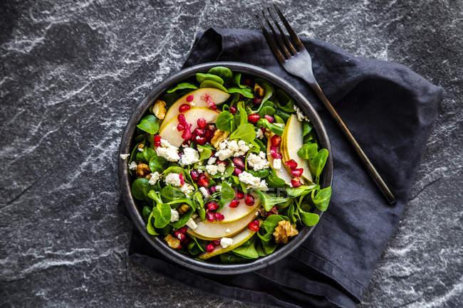 Ciotola di insalata mista con lattuga di agnello, feta, pera, semi di melograno e noci — Foto stock