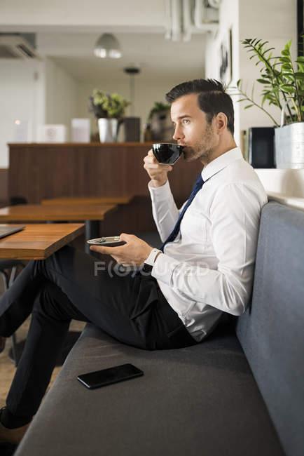 Бизнесмен наслаждается кофе и отдыхает на скамейке в кафе — стоковое фото