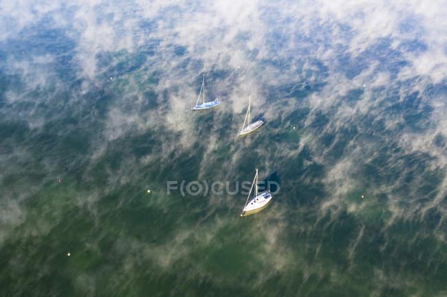Германия, Бавария, Уппер Бавария, Фуэнфзеэнланд, Санкт-Оле возле Мюнзинга, Вид с воздуха на озеро Штарнберг, салютные лодки и утренний туман — стоковое фото