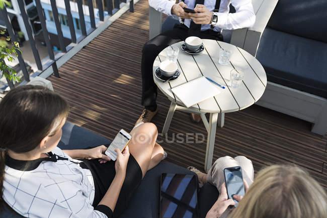 Трое коллег по бизнесу делают перерыв на кофе на городской террасе, проверяют смартфоны — стоковое фото