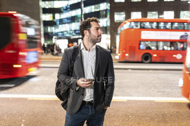 UK, London, businessman standing next to a busy street at night — Photo de stock