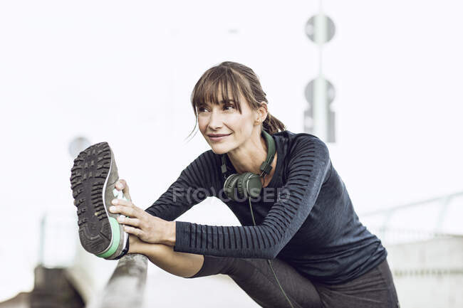 Sportive woman doing her fitness training outdoors, stretching — Stock Photo