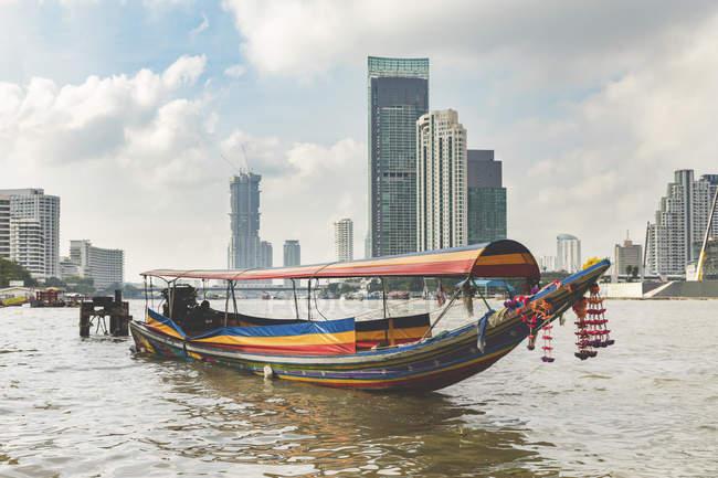 Thaïlande, Bangkok, bateau typique sur la rivière Chao Phraya avec des gratte-ciels en arrière-plan — Photo de stock