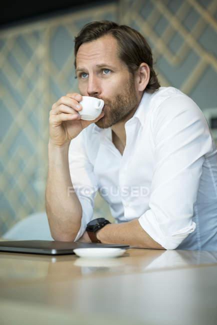 Случайный пенсионный предприниматель с эспрессо-брейком в офисном зале — стоковое фото