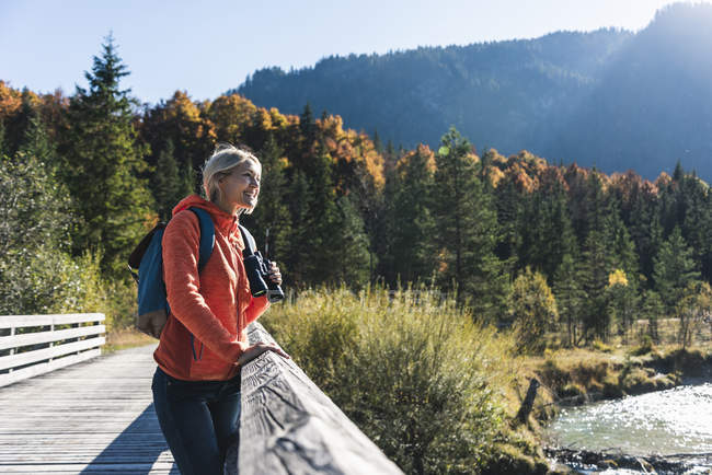 Austria, Alps, woman on a hiking trip standing on a bridge with binoculars — стокове фото