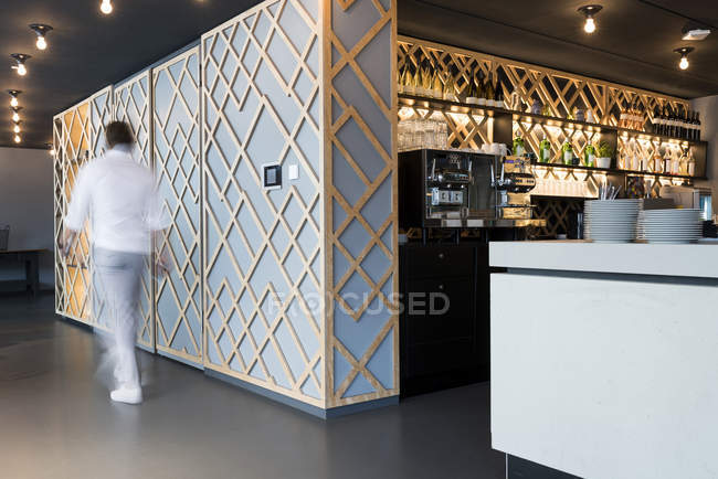 Blurred man walking past modern office lounge area and bar — Stock Photo