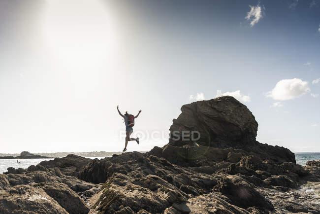 Jeune femme qui court et saute sur une plage rocheuse — Photo de stock