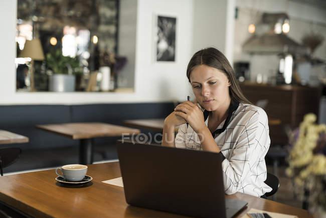 Молода бізнесменка в кафе, що працює з ноутбуком на дерев