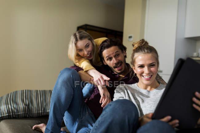 Freunde auf Couch im Wohnzimmer sitzen, Spaß haben, Laptop benutzen — Stockfoto