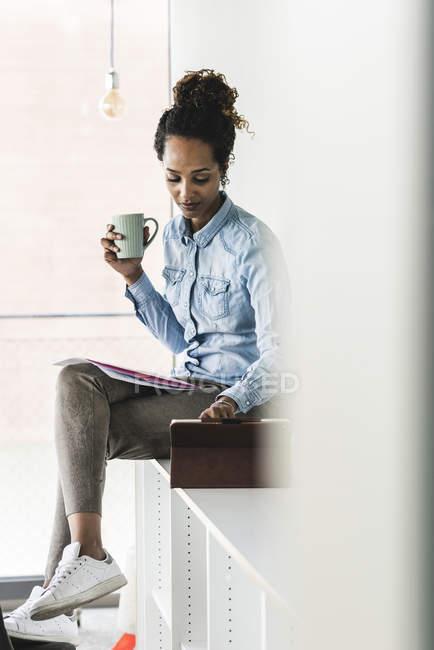Молодая бизнесвумен сидит на полке, используя цифровые планшеты, пьет кофе — стоковое фото