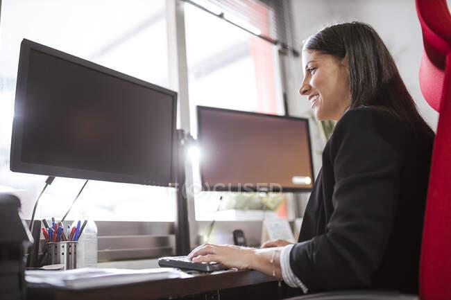 Улыбающаяся деловая женщина за компьютером, сидя в офисе на складе — стоковое фото