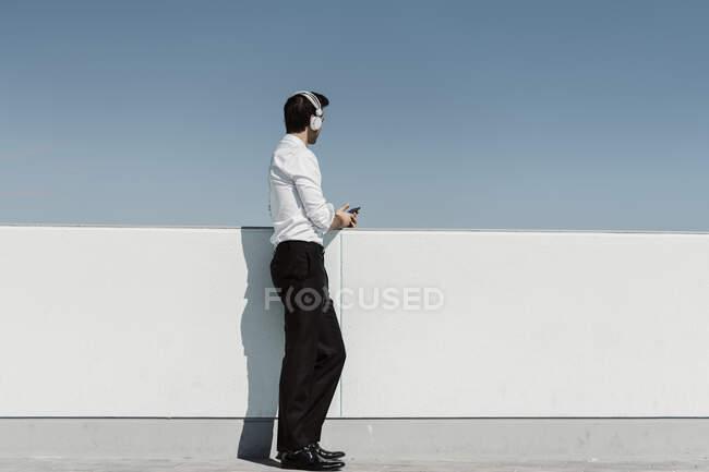 Бизнесмен слушает музыку с наушниками и смартфоном на террасе на крыше — стоковое фото