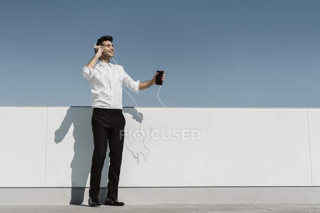 Счастливый бизнесмен слушает музыку с наушниками и смартфоном на террасе на крыше — стоковое фото