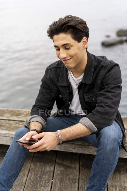 Denmark Copenhagen smiling young man sitting at the waterfront using cell phone — Stock Photo