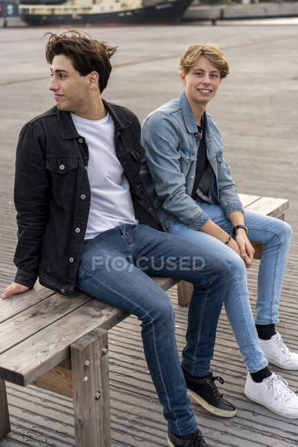 Данія, Копенгаген, двоє молодих чоловіків сидять на лавці. — стокове фото