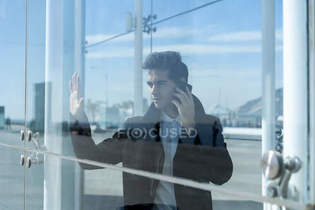 Empresario al teléfono en la ciudad detrás del cristal - foto de stock