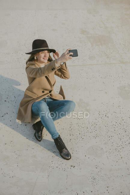 Joven hipster mujer sentado en el suelo haciendo un selfie - foto de stock