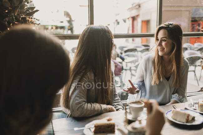 Three happy young women meeting in a cafe — Stockfoto
