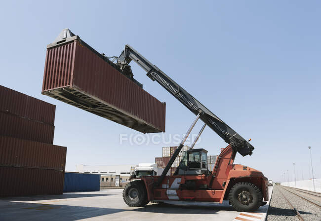 Crane lifting cargo container near railway tracks on industrial site — Stock Photo