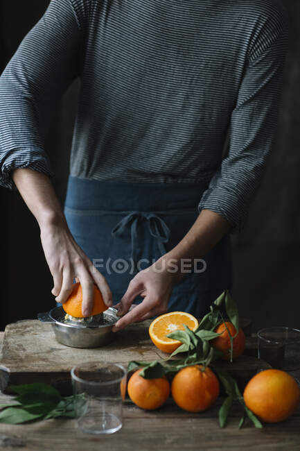 Young man squeezing orange, partial view — Stock Photo