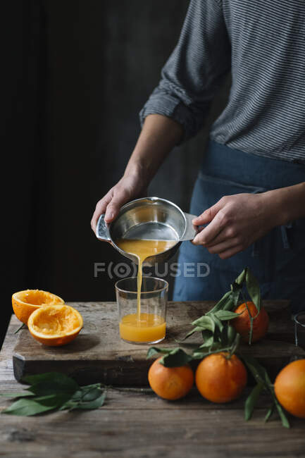 Young man pouring freshly squeezed orange juice into a glass, partial view — Stock Photo