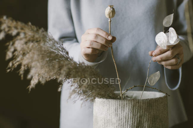 Woman decorating grasses and flowers, partial view — Stock Photo