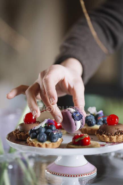Рука женщины расставляет Макарона на торте, крупным планом — Stock Photo
