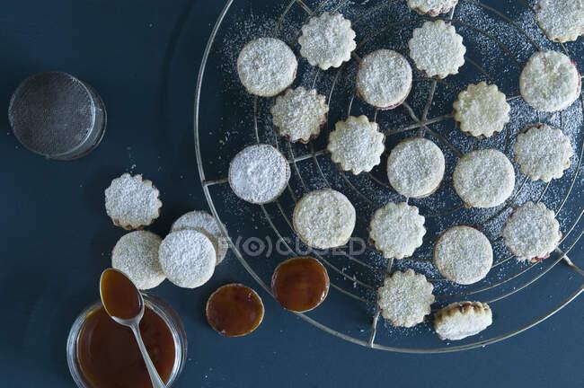 Рождественские печенья Spitzbuben на выпечке сетке, варенье в банке, шиповник варенье, глазурь сахар — Stock Photo