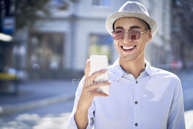 Giovane felice guardando il cellulare in città — Foto stock