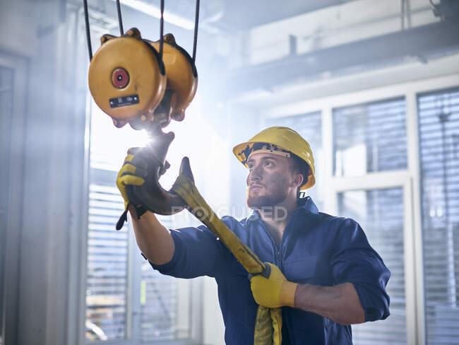Промисловий працівник фіксує підйом шпори на криївку. — стокове фото
