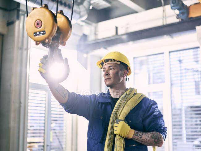 Industriearbeiter fixiert Hebegurt auf Innenkran — Stockfoto