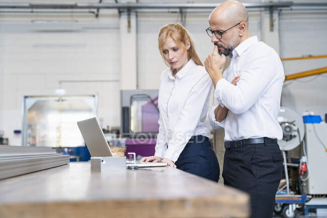 Businessman and businesswoman using laptop in factory — Stock Photo