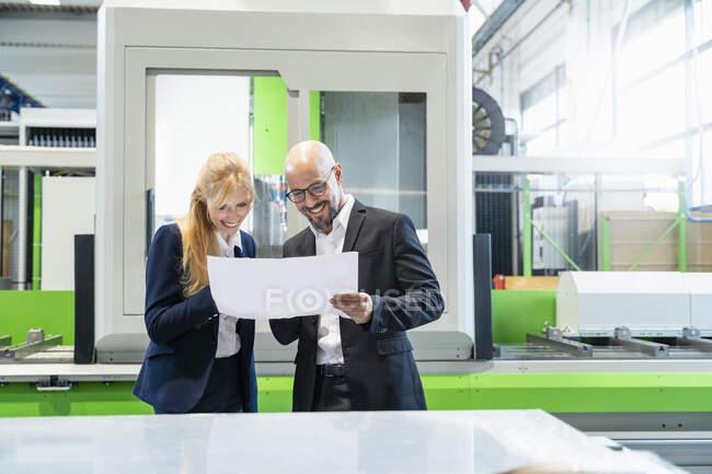 Hombre de negocios sonriente y mujer de negocios mirando el plan en la fábrica - foto de stock
