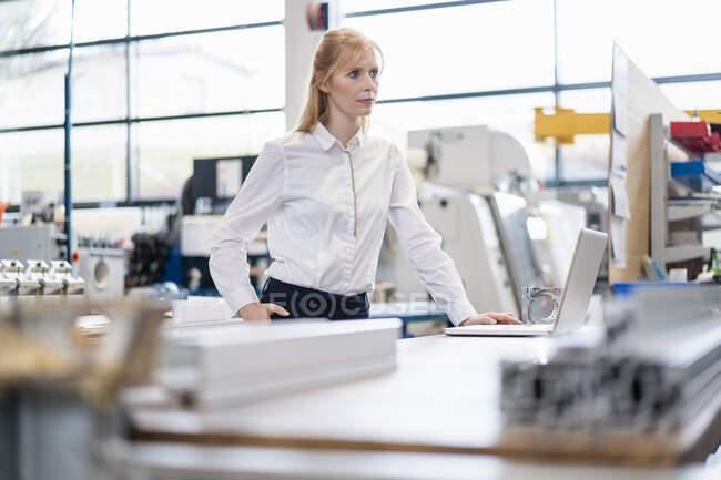Empresária com laptop na fábrica — Fotografia de Stock