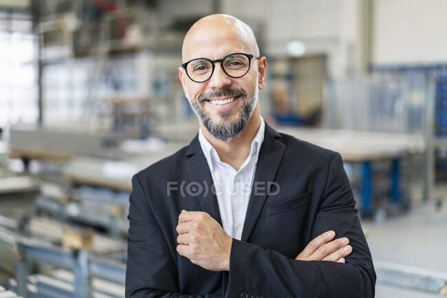 Portrait of smiling businessman in factory — Stock Photo