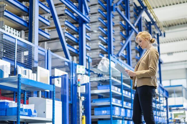 Безробітна жінка з планшетом на фабриці. — стокове фото
