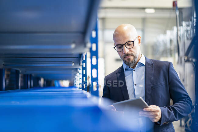 Businessman with tablet in factory storehouse — Stock Photo
