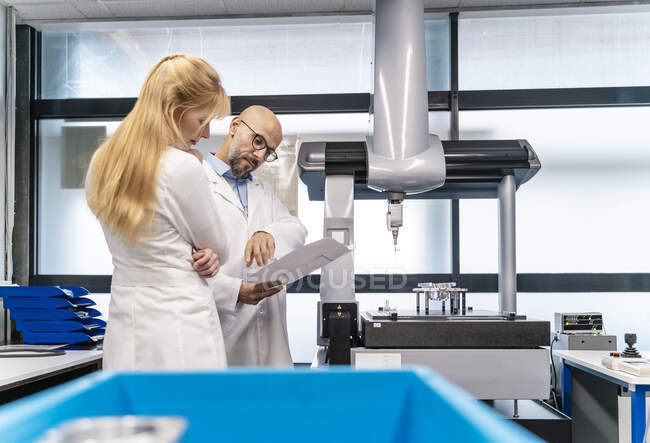 Two technicians wearing lab coats looking at plan — Stock Photo