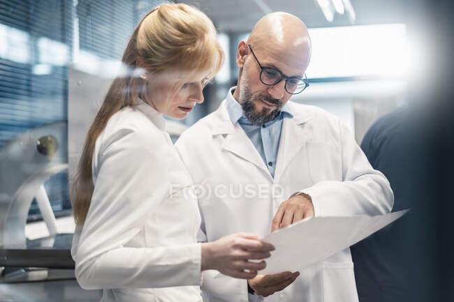 Deux techniciens en blouse de laboratoire regardant le plan — Photo de stock