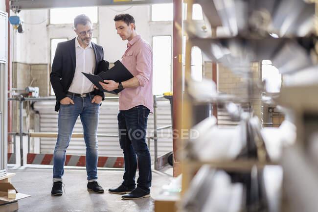 Dos hombres con portapapeles hablando en el almacén de la fábrica - foto de stock
