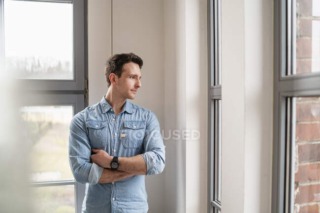 Businessman looking out of window in office — Stock Photo
