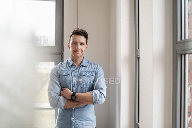 Retrato del hombre de negocios confiado en la ventana en la oficina - foto de stock