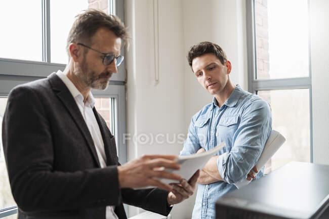 Dos colegas mirando papeles en la ventana de la oficina - foto de stock