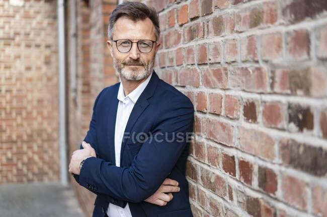 Портрет довірливого бізнесмена біля цегляної стіни. — стокове фото