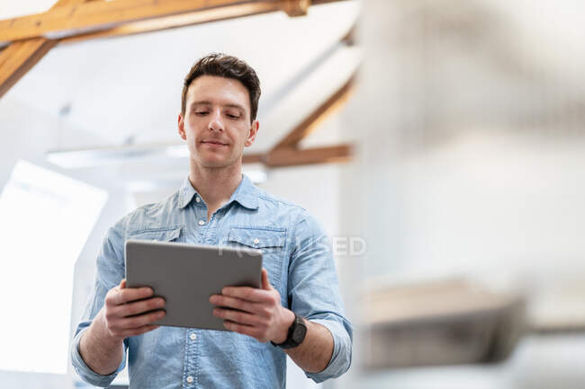 Portrait of young businessman using tablet in office — Stock Photo