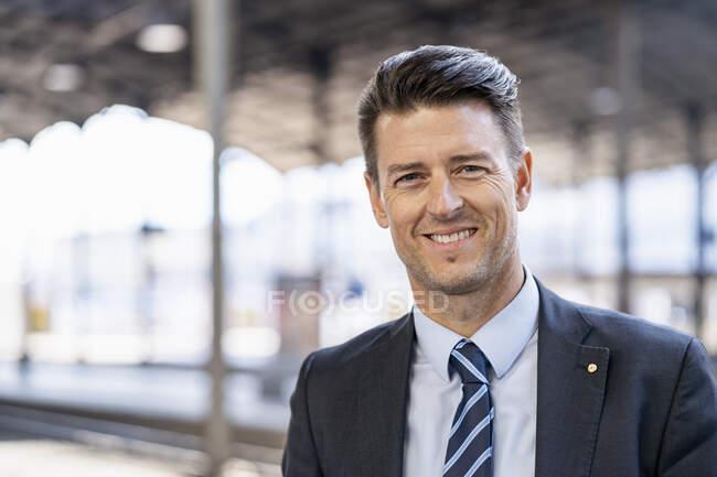 Portrait of smiling businessman at station platform — Stock Photo